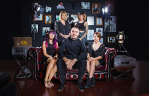 A corporate portrait of a hair salon team sat on and around a stylish red leather couch