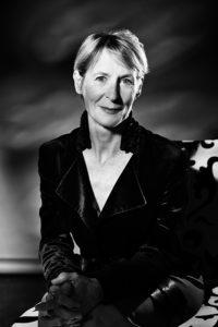 A creative corporate portrait of a woman lit in a dappled light