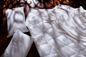 Product photography of a duvet and pillow bedding set shot in a dappled light scattering across a timber floor