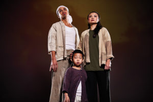 An image of 3 dejected-looking actors in a theatre performance of 'Miss Saigon'.