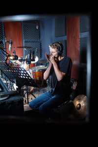 An image of a man playing a harmonica in a recording studio
