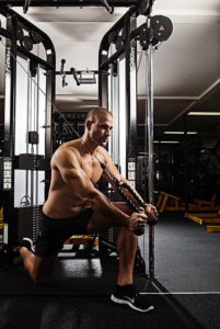 Image of a man in a gym performing a cable machine exercise