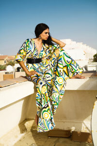 An image of a dark-skinned woman sitting on the roof of a villa in a colourful silk summer dress