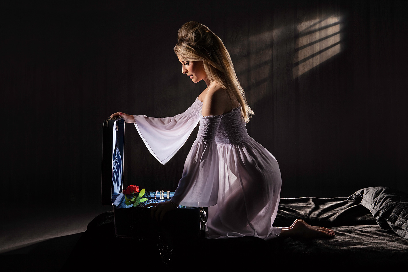 Photo of a young woman kneeling on her bed at night in a semi-transparent night gown, opening a suitcase. A shaft of light is cast across the wall behind her from a window.