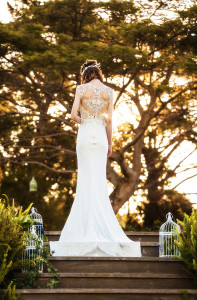 Photo from behind of a bride standing in front of trees and a sunset in her wedding gown designed by Gold Coast Bridal Lounge, Australia