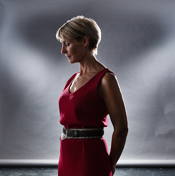 A_corporate_portrait_of_a_womans_side_profile_against_grey_studio_backdrop