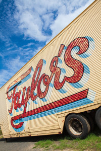 An image of eroded typographic sign writing on the side of a truck with a background of blue sunny sky