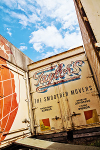 An image of eroded typographic sign writing on the side of trucks and shipping containers with a background of blue sunny sky