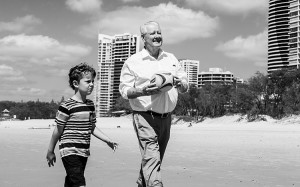 An image of a boy walking on a beach with his grandfather holding a rugby ball.