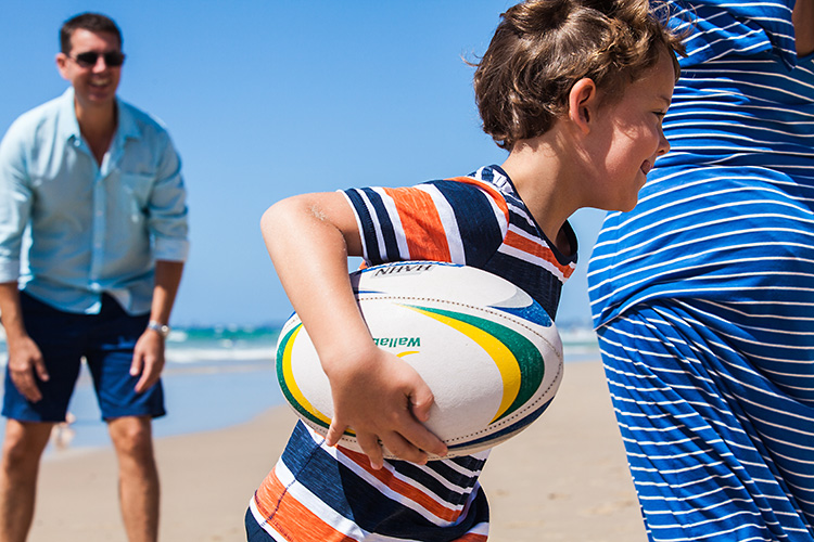An image of a boy on a beach running with a rugby ball