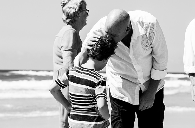 An image of a father on a beach kissing his son's head.