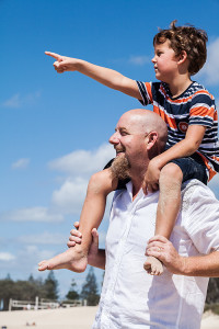 An image of a boy sitting on his father's shoulders on a beach.