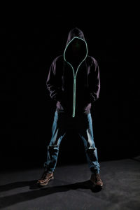 A man standing in the darkness modelling a black urbanwear hooded jumper/sweater with LED piping