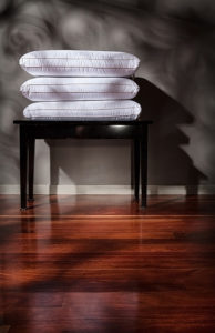 Product photography of pillows stacked on a black stool against a grey wall above a timber floor in a beautiful dappled light.