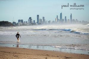 A surfer exits the sea on a Gold Coast beach in Australia